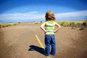 Child standing alone on a road