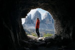 man in cave looking at mountains