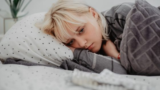 depressed young woman lying in her bed