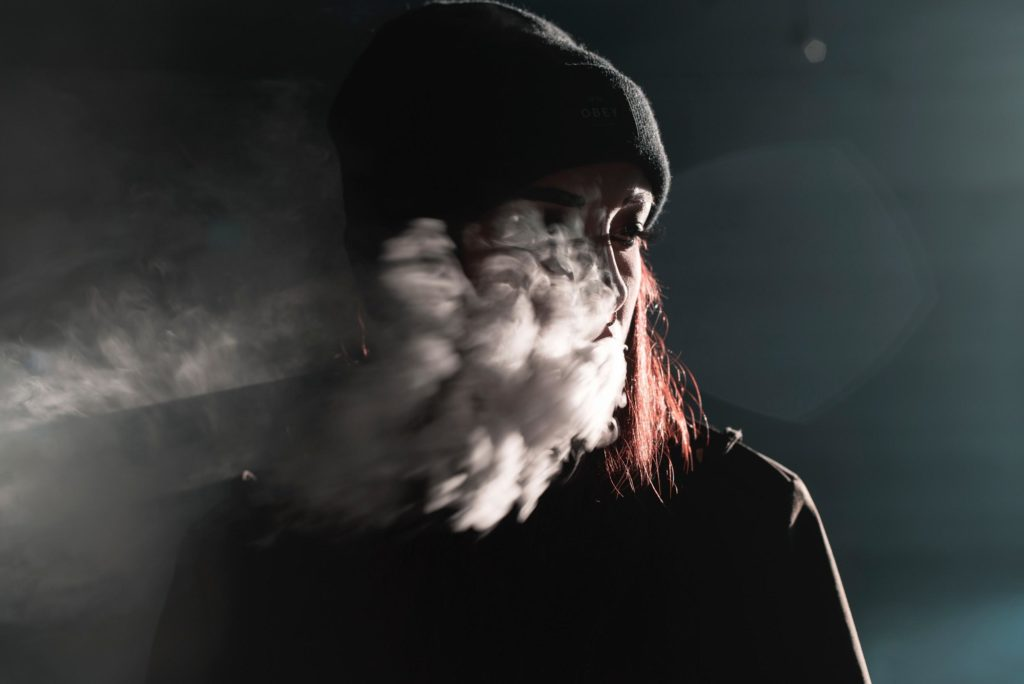 girl smoking and exhaling clouds of smoke