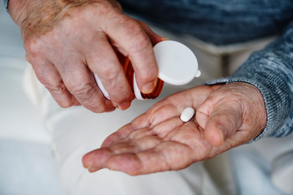 older man taking a pill