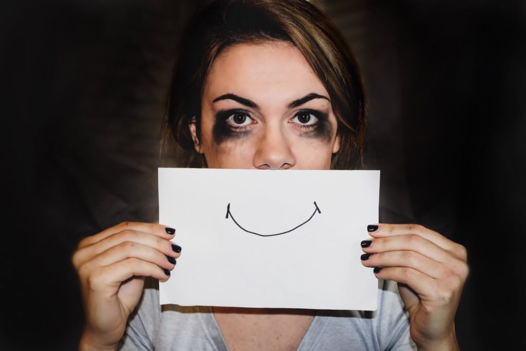 woman with smeared eye makeup holds a paper with a smile