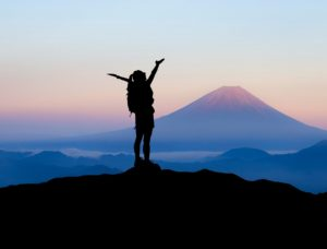 women in victory at top of mountain